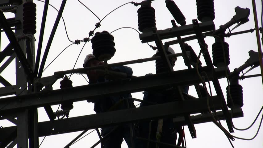 Electricians in a bucket fixing high voltage electrical lines