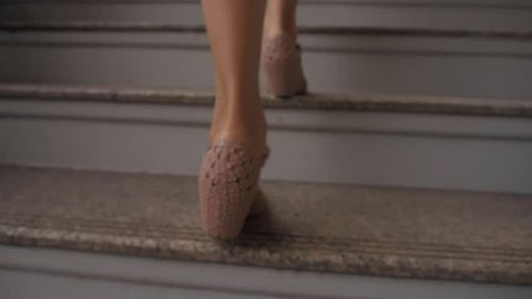 Woman Legs Walking Up the Stairs. Woman in Short Light Blue Dress. View from the Back.
