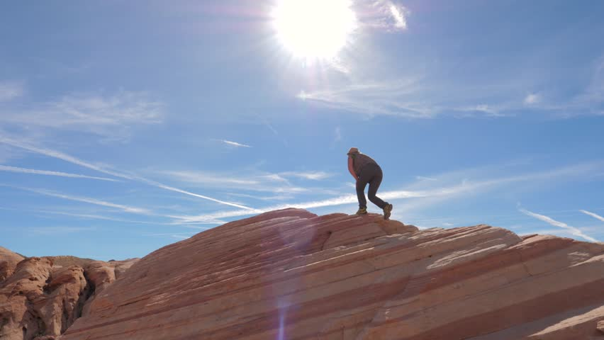 Hiking active sporty woman in UV protection outdoor clothing. Climbing up the ridge to the top of Red Rock. The bottom view of the lady silhouette against the blue sky and sun. Slow Motion, 4K