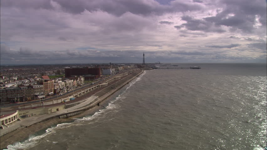 AERIAL United Kingdom-Over Blackpool Piers 2005: Run down Golden Mile from the north and back in closer shots