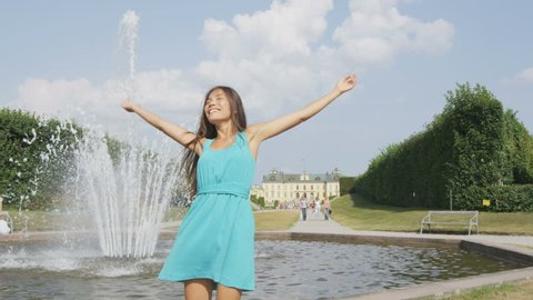 Woman in Stockholm having fun at park fountain at Drottningholm palace, Sweden. Tourist girl visiting the Queen's royal residence, a famous attraction. Asian caucasian biracial woman in Scandinavia.