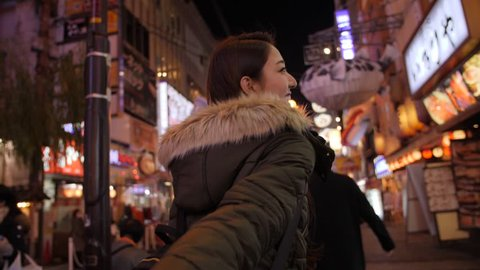 Japanese woman walking through dotombori Japan night life POV