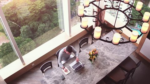 Top view of man at big office desk. Clean working space at huge table businessman working on laptop and writing something to notebook. Big windows at background.