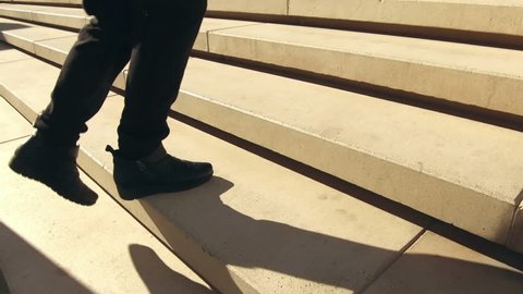 Climbing a stairs, low angle shot. Following some feet that go up a concrete stairs.Side view. Abstract Concept of improve, success, effort.