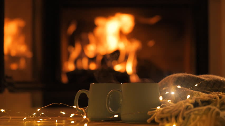 Steam from a cups with a hot cocoa on the fireplace background.   Decoration garlands of lights .  | Shutterstock HD Video #1006610386
