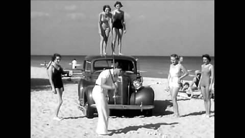 CIRCA 1937\xD1 A golfer hits golf balls at the beach and off of his car while women wearing swimsuits look on.
