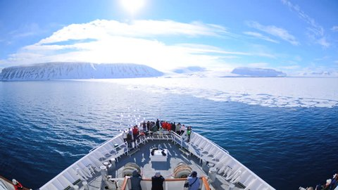 CIRCA 2010s - A POV time lapse shot of a ship bow, icebergs and tourists passing through Lomfjorden near Svalbard, Norway on an icebreaker ship.