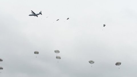 CIRCA 2010s - U.S. Army paratroopers parachute from a plane in a large military exercise.