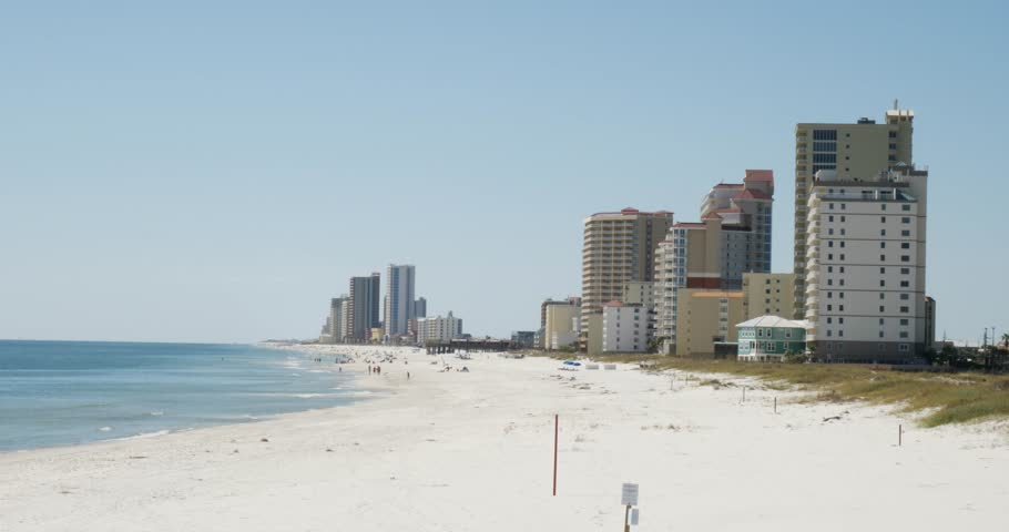 View along a wide sandy tropical beach to high rise apartment blocks, condominiums or hotel accommodation in a static clip