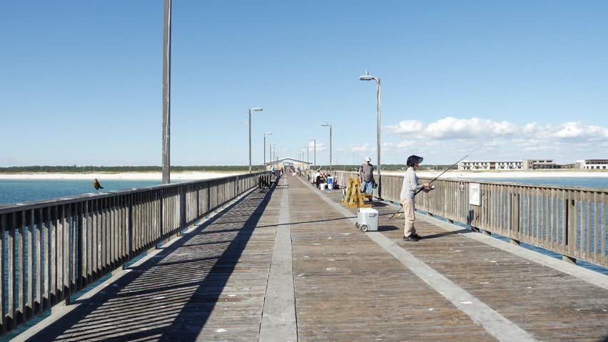 Gulf Shores Alabama Oct 2017 Full length of people fishing on an old pier in a sunny day at the seaside in an idyllic travel destination