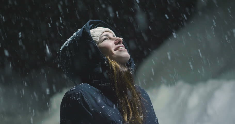 As the snow falls from the sky, a beautiful woman at night stops in a light and starts playing, breathing clean air and dancing in the middle of nature.