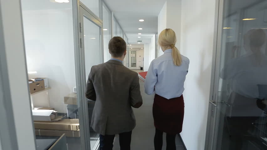 A pair pf colleagues are going throught the office and talking. Male and female managers are walking in the corridor with glass walls and coming to big reception with sofa, lockers and wooden counter