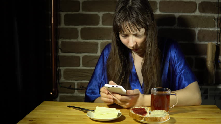 A Young Sleepy Woman In A Blue Robe Browses The Video On Her Smartphone And Drinks Tea Sitting Next To A Brick Wall 4k