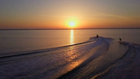 Jet ski rides water skiing man in the sunset drone footage
