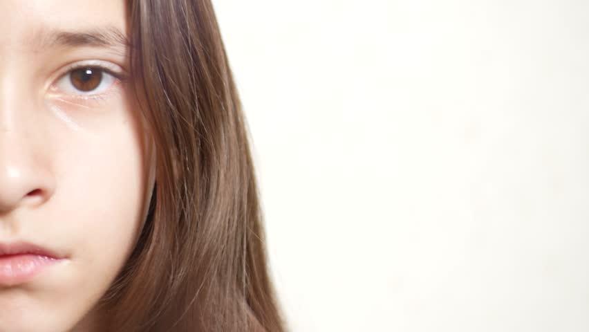 Young sad girl looks at the camera. 4k. close-up half face, eye close-up. copy space