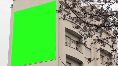 Billboard with Green Screen on a Building. Ready to replace green screen with any footage or picture you want.