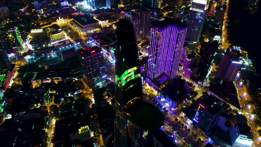 Aerial: A night time shot of Downtown Saigon (Ho Chi Minh City) business district. Featuring a slow revolve of an iconic feature within the Saigon city center.