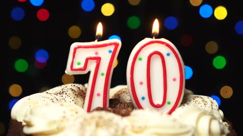 Number 70 on top of cake - seventy birthday candle burning - blow out at the end. Color blurred background.
