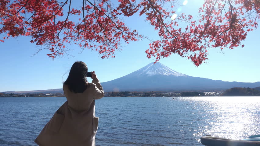 Young girl take photo and seeview Fuji Mountain and Maple Leaf  red color  in autumn season lake view Lake Kawaguchi Japan