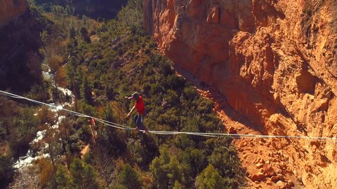 Slow motion with a young  brave man slacklining , highlining above a big canyon . Nature Adventure and leisure sport . Mountain Balance Extreme Hiker Walking Happy, 4k aerial cinematic footage
