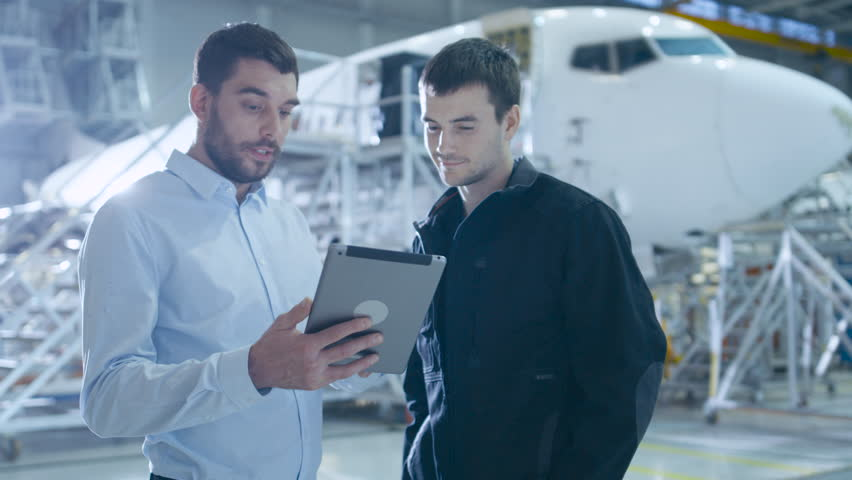 Aircraft Maintenance Worker and Engineer having Conversation. Holding Tablet. Shot on UHD 4K Camera.