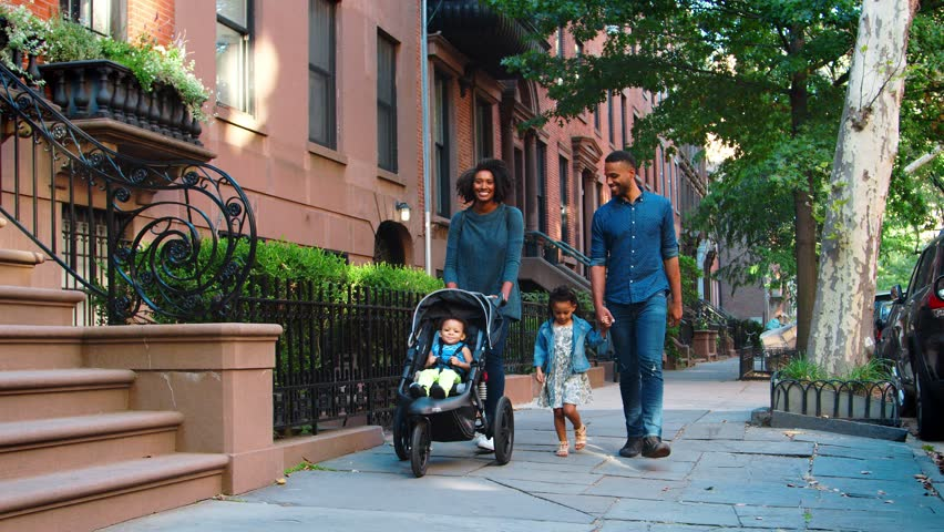 Young black family with stroller walking in Brooklyn street
