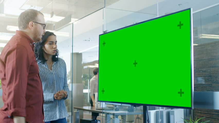 Male and Female Business People in Conference Room Have Discussion about Mock-up Chroma Key Green Screen TV. Shot on RED EPIC-W 8K Helium Cinema Camera.