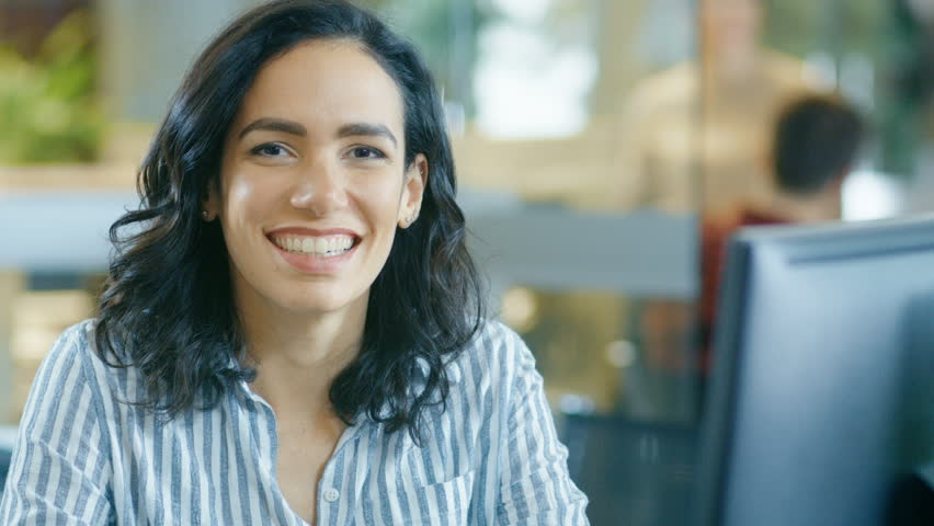 Portrait Shot of a Beautiful Young Hispanic Woman Working on a Computer, Smiling Warmly on the Camera. In the Background Busy Office with Working Colleagues. Shot on RED EPIC-W 8K Helium Cinema Camera