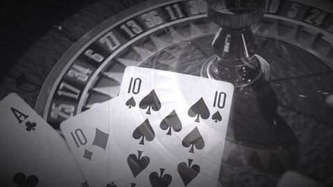 Close up of spinning roulette wheel in casino with superimposition of rolling dice and playing cards playing hands made like an old movie film in black and white