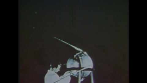 1960s: Scientist operates Sputnik 1 satellite. Space rocket takes off, smoke. Laika space dog. Space rocket flies in the sky.