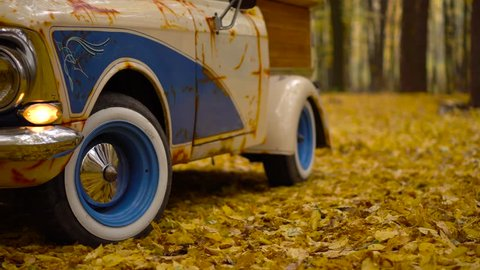 Retro car old Moskvich with wooden customized luggage in the autumn forest