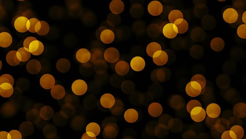 Golden glitter particles on dark background.