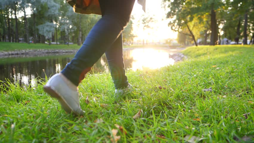 Time out pleasure, elegant woman walk at quiet park on grass at pond bank, low camera, slow motion glide shot. Small silver shoes step on autumn lawn, wonderful evening sun light ahead