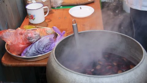 Beverage brewing in huge cauldron in yard to warm poor people, charity kitchen