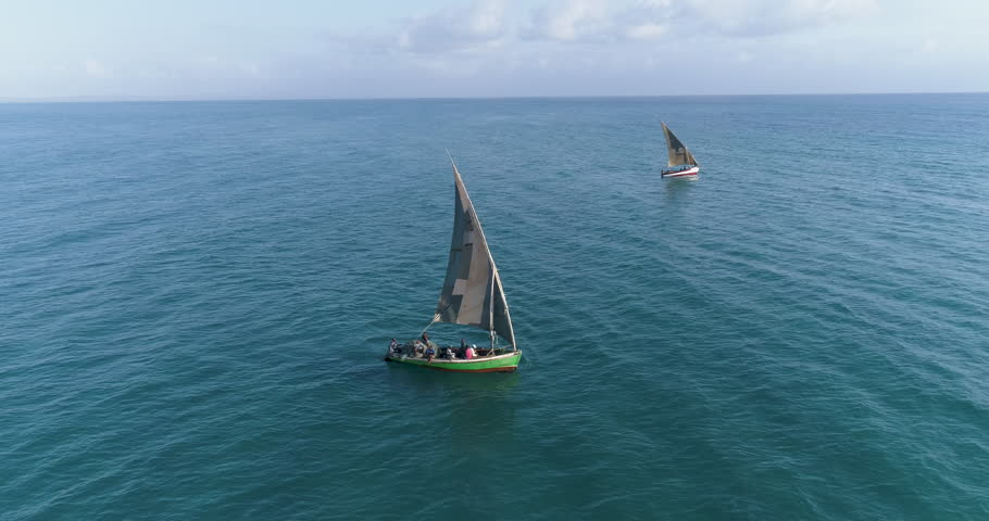 Aerial close-up view of two traditional dhow fishing boats heading out to sea for the days fishing
