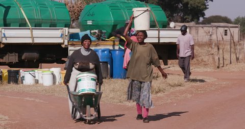 The plight for clean water. Two african woman collecting water from a remote tanker in plastic buckets and walking back to their homes due to a drought in Africa