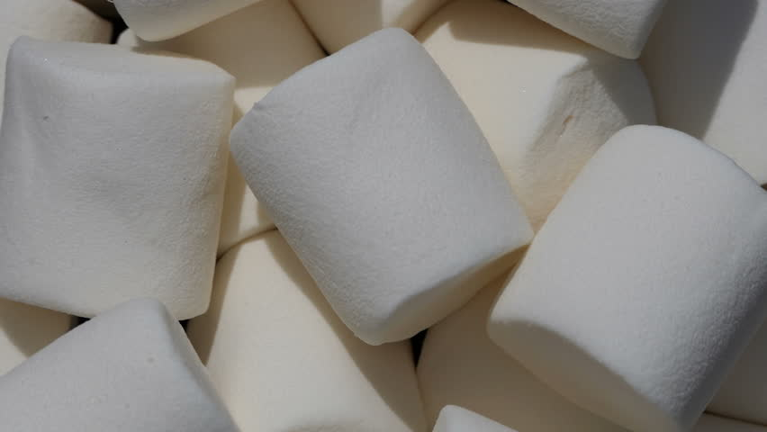 White Marshmallow heap rotation slowly top view. Soft Marshmallow rotating in slow motion with copy space 4k. beautiful Marshmallow background. Marshmallow texture