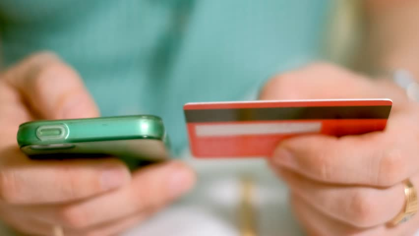 A man buys goods in an online store and pays a credit card through her phone 4k