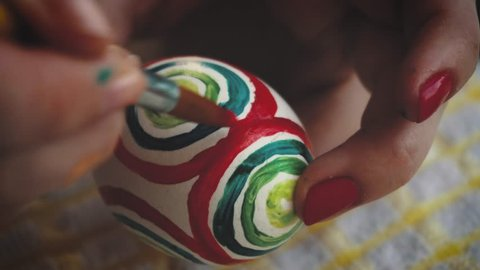 Female hand painted easter eggs with a brush. Passover.