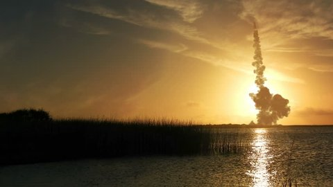 4k Futuristic or Sci-fi landscape.  Low setting sun with wonderful reflection and large rocket ship blasting off with enormous plume of smoke.