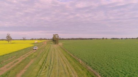 Aerial / Drone View Of Farmer Driving Down A Dusty Outback Road On A Farming Property