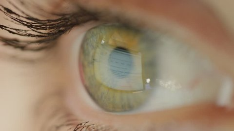 NEW YORK, USA - 4 JUNE 2017: MACRO Green eyed woman using Google search tool for surfing web. Internet Google search engine reflecting in eye surface. Female Googling for information over web browser