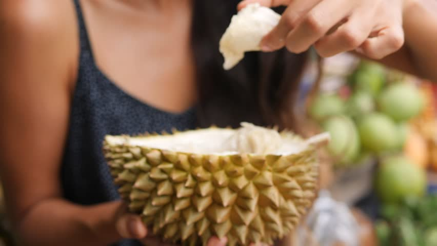 Attractive Tourist Woman Trying and Eating Exotic Durian Fruit. 4K, Bali, Indonesia.