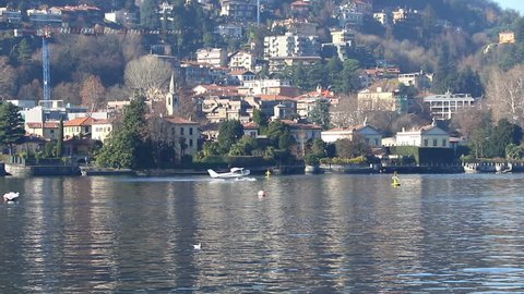 Seaplane aircraft floats on the water and takes off from Water Aerodrome of Como lake, Lombardy, Italy. Since 1913 Como is home to the only seaplane school in Europe