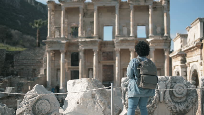 Celcus library at Ephesus ancient city Izmir Turkey. The tourist,in jeans African woman with brown backpack and camera travels there.