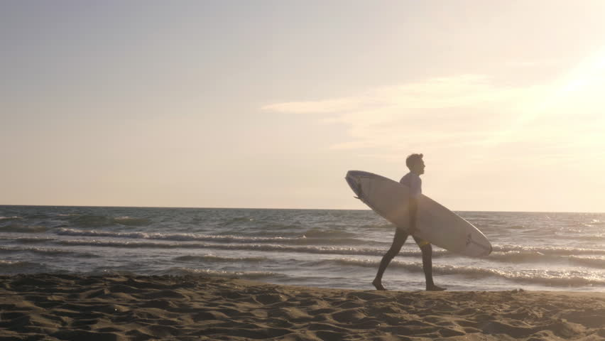 Young man surfer in wetsuit picks up surf board at the beach walking on the sand along sea shore looking at the ocean at sunset gimbal dolly steadycam