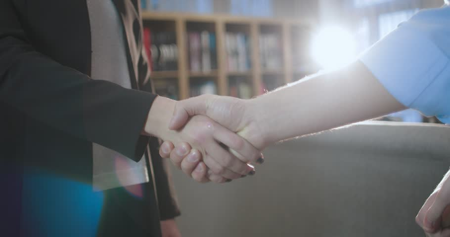 Business handshake. Businesswoman meets partners in her office. She shakes hands with her guests and offers to go inside. in slow motion | Shutterstock HD Video #1007111326
