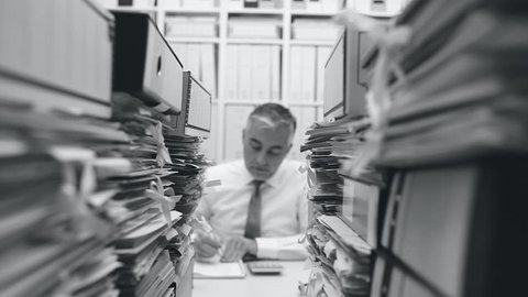 Tired overworked businessman working in the office, his desk is filled with paperwork: work overload and stress concept, dolly shot