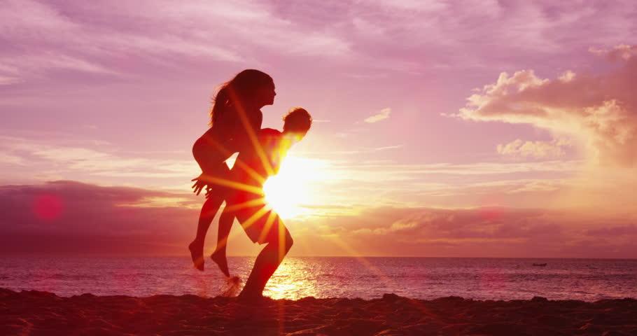 Couple on beach having fun happy doing piggyback enjoying sunset on romantic summer travel vacation holiday honeymoon. #1007123956