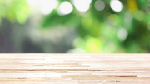 Wood table top with blur natural green foliage bokeh in background - can be used for display and montage your products or foods